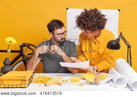 Concentrated Woman And Man Collaborate On Information Pose At Desktop During Working Time In Modern