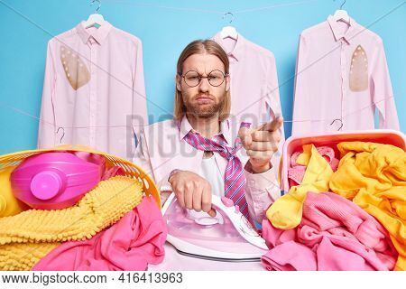 Fatigue Househusband Busy Ironing Laundry At Home Poses With Electric Iron Baskets Full Of Dirty Lin
