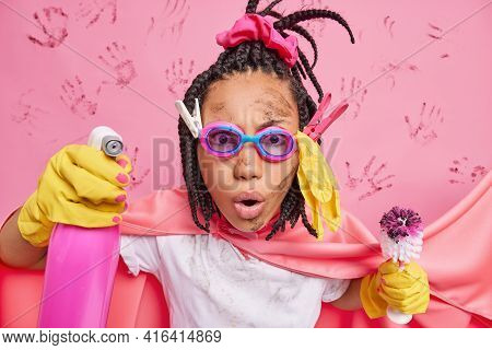 Super House Cleaning. Stunned Housewife With Dreadlocks Holds Spray Detergent Toilet Brush Cleans Ro
