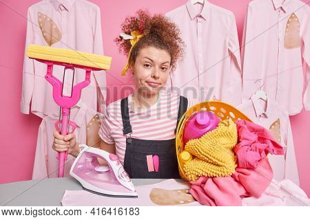 Serious Young Woman With Curly Hair Holds Mop And Basket Of Cleaning Laundry Irons Washed Linen At H