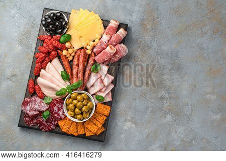 Meat And Cheese Appetiser, Olives And Basil On A Gray Background. Top View With Copy Space.