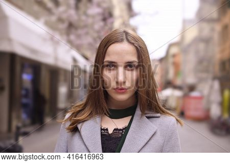 Portrait Of A Girl In The City. Beautiful Young Woman In A Gray Coat, European. Horizontal Format, C