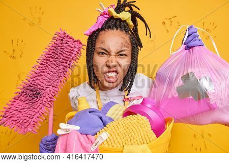 Irritated Young Afro American Woman With Dreadlocks Clenches Teeth And Looks Angrily Takes Out Rubbi