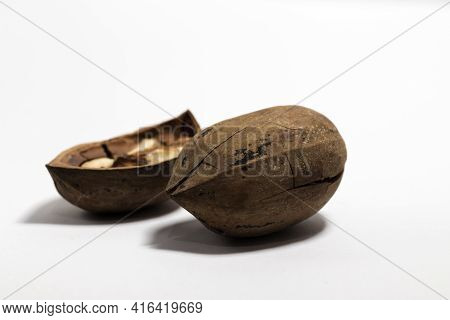 Close-up Of A Broken Pecan Nuts, One Broken, On A White Background