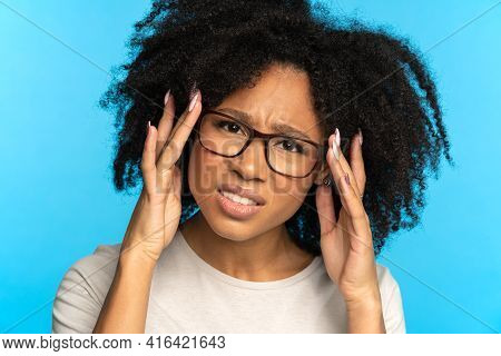 Studio Portrait Of Unsure Doubtful African American Girl Touching Glasses, Looking At Camera, Isolat