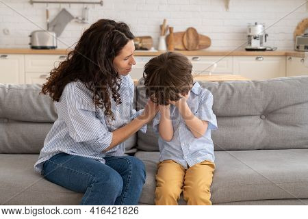 Closeup Of Worried Mother Calm Weeping Kid. Upset Little Boy Cry Sit On Couch Together With Caring M
