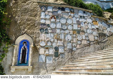 Wall Nearby Assumption Cave Monastery With Storage Of Grounds From Different Holy Places. Icon Of Ig