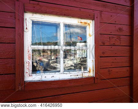 Old Wooden Window With Reflection Of A Red Wood House And Space For Graphics And Text