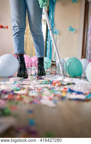 Woman With Pushbroom Cleaning Mess Of Floor In Room After Party Confetti