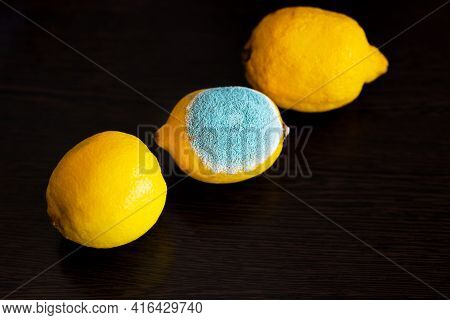 Three Whole Yellow Bright Lemons On A Dark Wooden Table. One Lemon With Light Turquoise Textured Mol