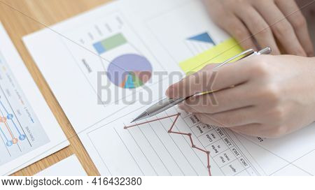 Businessmen working in the office using the expense and budget accounting calculator with graphs as
