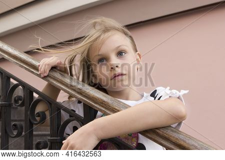 Portrait Of A Stylish Model Of A Sad Girl Child Of Six Seven Years Old With Blond Hair On The Backgr