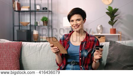 Caucasian Short Haired Brunette Woman Wearing Plaid Shirt Looking At Credit Card While Going To Do O