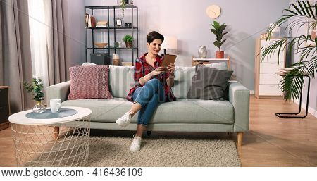 Happy Young Caucasian Woman Gesturing While Relaxing On Sofa At Home And Speaking Using Tablet. Smil