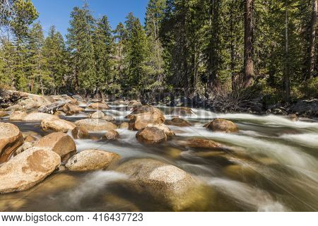 Wild Merced river with turquoise water and many boulders in Yosemite National Park. Long exposure. California, USA