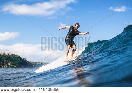 December 09, 2020. Bali, Indonesia. Surfer On Longboard In Ocean During Surfing.