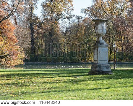 White Vase Sculpture In Neoclassical Style Next To The Pond In Public Park During An Autumn Day In P