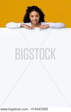 Beautiful Smiling African American Female Leaning On Blank White Advertisement Board