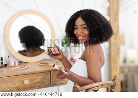 Black Woman Applying Makeup In Front Of Mirror, Sitting At Dressing Table With Eye Shadow Palette, S