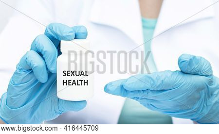 Doctor In A White Coat And Blue Sterile Gloves Holding A Jar With Text Sexual Health. Medical Concep
