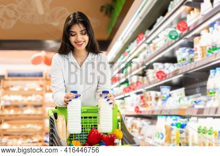 Cheerful Arabic Woman Doing Grocery Shopping Buying Milk In Supermarket