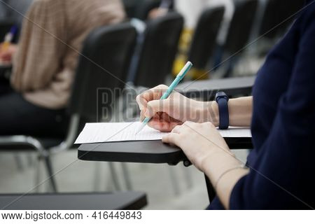 A Girl Writes A Dictation Or Fills Out Documents In The Audience, Sitting On A School Chair With A W