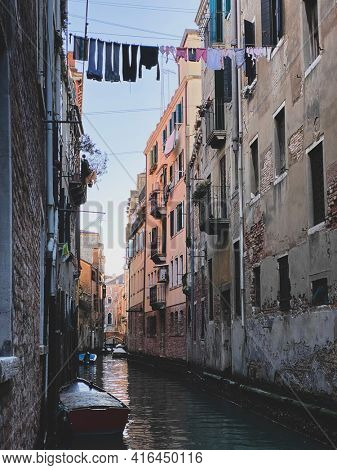 Picturesque little canal street in Venice with a boat and clothes drying in the sun