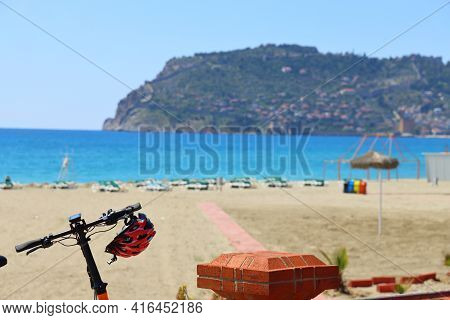 Protective Helmet On The Handlebars Of A Bicycle Against The Backdrop Of A Deserted Beach, Sea And C