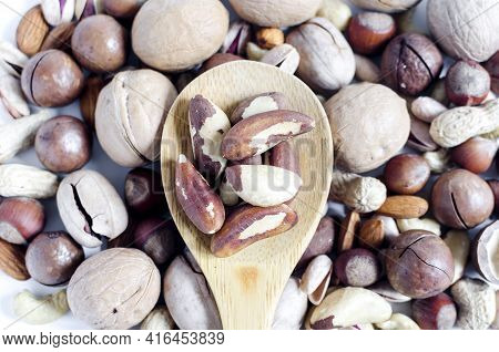 Brazil Nut In A Wooden Spoon On The Background Of A Scattering Of Different Nuts Assorted Nuts