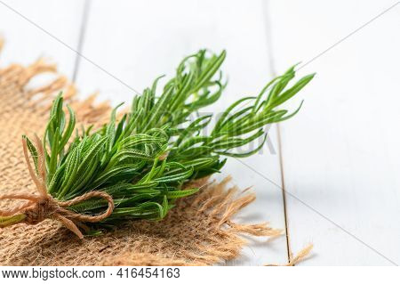 Branch Of Fresh Rosemary On Sack And White Wood Background. Rosemary Is A Rich Source Of Antioxidant