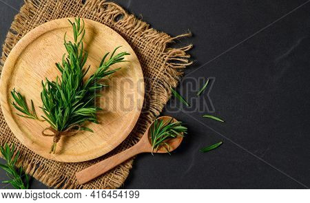 Top View Of Branch Fresh Rosemary In Wood Plate  On Black  Background. Rosemary Is A Rich Source Of