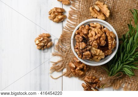 Top View Of Walnut In White Cup On Wood Background. Healthy Nuts Concept. Walnuts Are An Excellent S