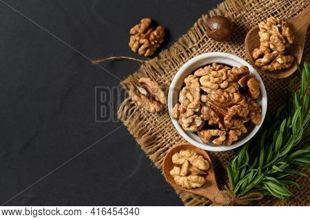 Top View Of Walnut In White Cup On Black Background. Healthy Nuts Concept. Walnuts Are An Excellent