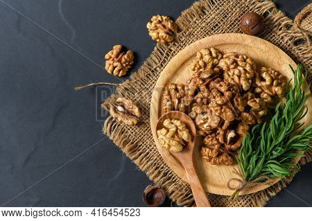 Walnuts And Rosemary Leaf In Wood Plate  On Black Table Background. Healthy Nuts Concept. Walnuts Ar