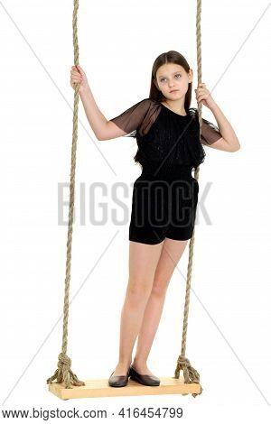 Joyful Girl Swinging On Rope Swing. Photo Session In The Studio