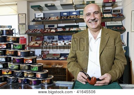 Portrait of a happy middle-aged tobacco shop owner with cans on display