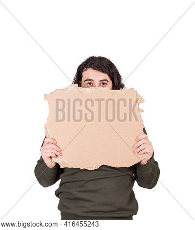 Fearful Man, Refugee Or Beggar, Holding A Blank Cardboard Sheet, Copy Space For Messages. Empty Bann