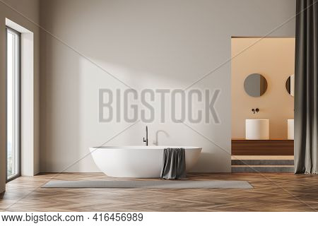 Light Bathroom Interior With White Bathtub And Towel, Grey Carpet And Window With Sunlight. Sinks Wi