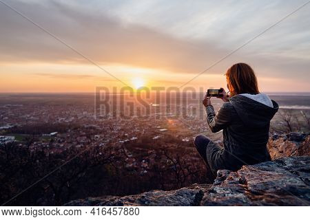 Young Woman Photographing Sunset. Young Woman Enjoying Sunset Over Small Town. Beautiful People. Hap