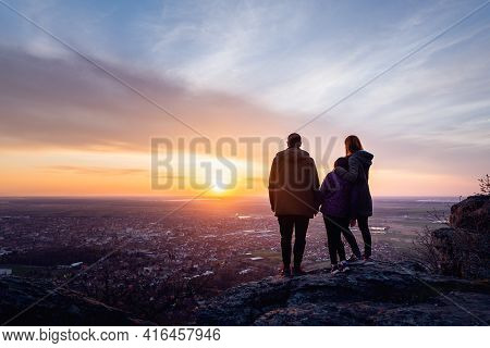 Family Enjoying Sunset From Mountain View. Young Happy Family Enjoying Sunset Over Small Town. Beaut