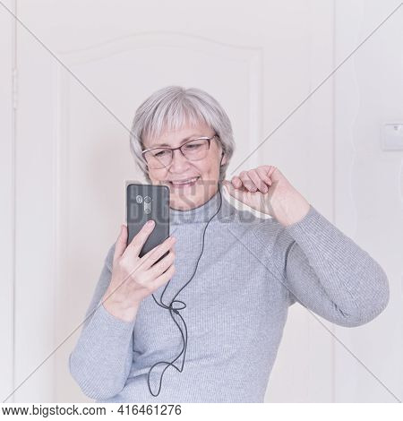 A Gray-haired Senior Woman With Glasses And A Gray Turtleneck Talking On Mobile Phone At Home. Peopl