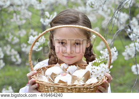 Girl In A Traditional Embroidered Shirt In A Blooming Cherry Garden.kid With Colored Eggs And Tradit