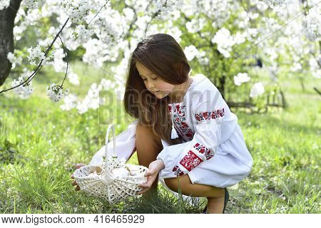 Girl Holding Basket With Colored Eggs And Traditional Easter Cake.girl In A Traditional Embroidered