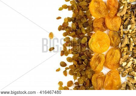 Walnuts, Dried Apricots And Raisins On A White Background With Place For Text. Background From Dried