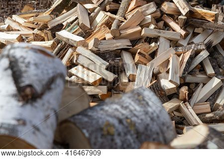 Chopped Firewood Stacked. Wood Heating Season. Chopped Firewood Of Different Trees