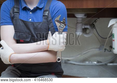 A Plumber With A Special Tool Repairs The Equipment.