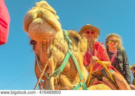 Couple Camel Riding In Australian Desert Of Northern Territory. Caucasian Tourists Enjoys Camel Ride