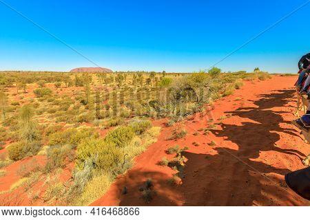 Uluru, Australia - Aug 2019:shadow Of People On Camel Riding In Australian Desert Of Northern Territ