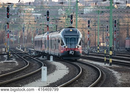 Untitled Red Passenger Train Arrival At Railway Train Station. Platform Track Front View. Public Tra