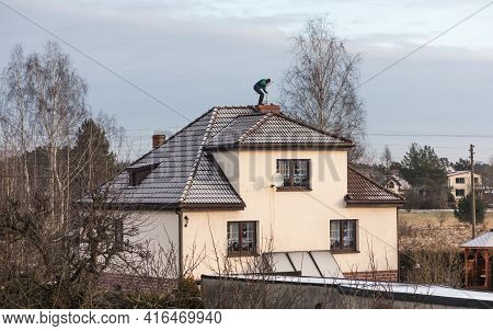 A Chimney Sweep Cleans The Chimney On The Roof Of A Detached House In Winter